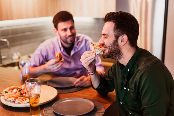 Two guys enjoying eating pizza at home stock photo