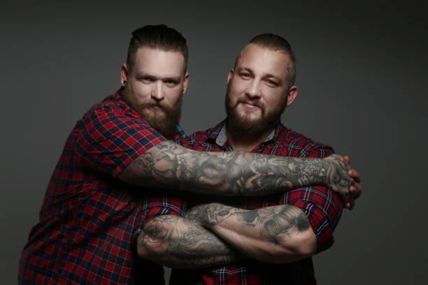 dos hombres en camisas rojas con la barba y tatuajes. - hombres grandes musculosos fotografías e imágenes de stock