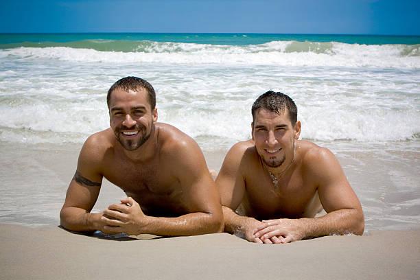zwei männer auf urlaub - fkk strand stock-fotos und bilder