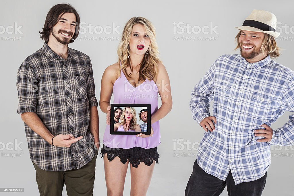 Two Guys One Girl And A Digital Tablet Royalty Free Stock Photo