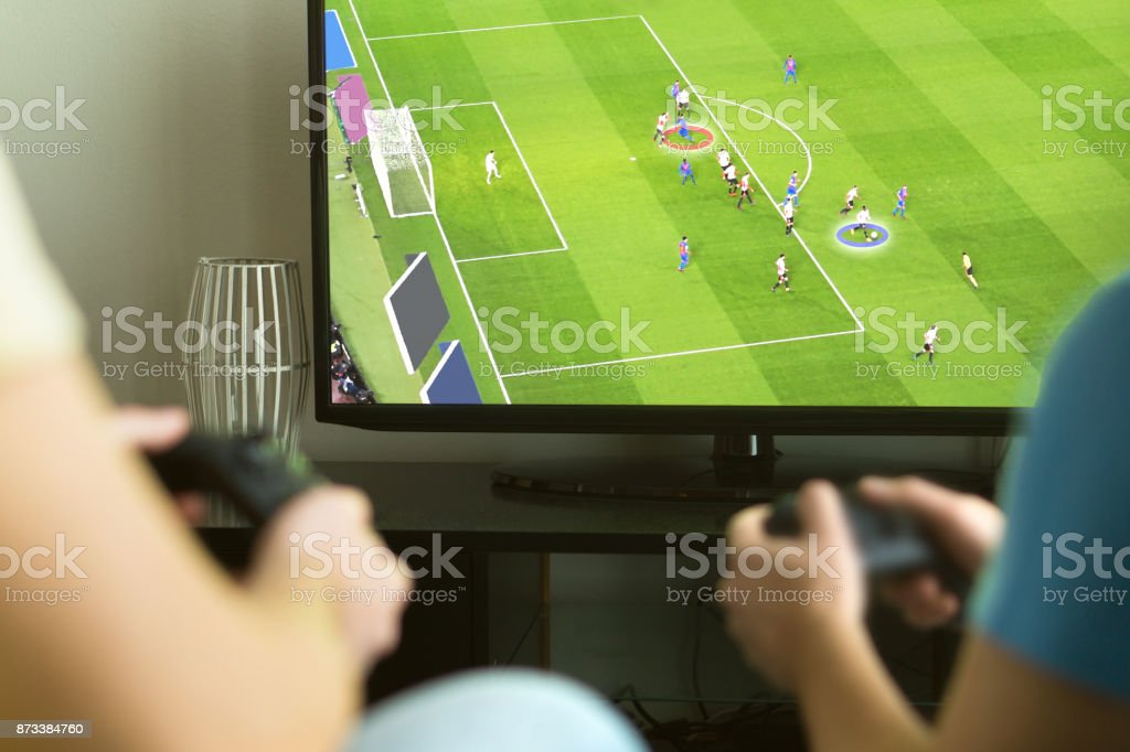 Two guys playing imaginary multiplayer soccer or football video game with console and tv. stock photo
