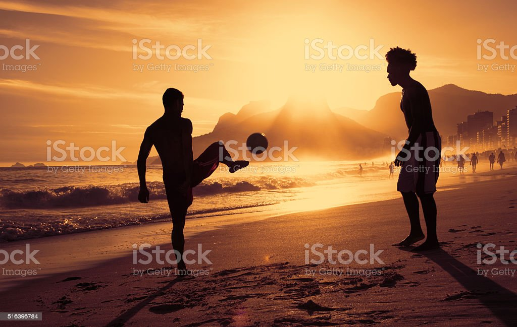 Two guys playing soccer at beach at Rio at sunset stock photo
