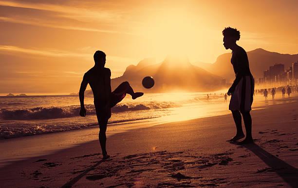 dois garotos jogando futebol na praia no rio ao pôr-do-sol - futebol de areia - fotografias e filmes do acervo
