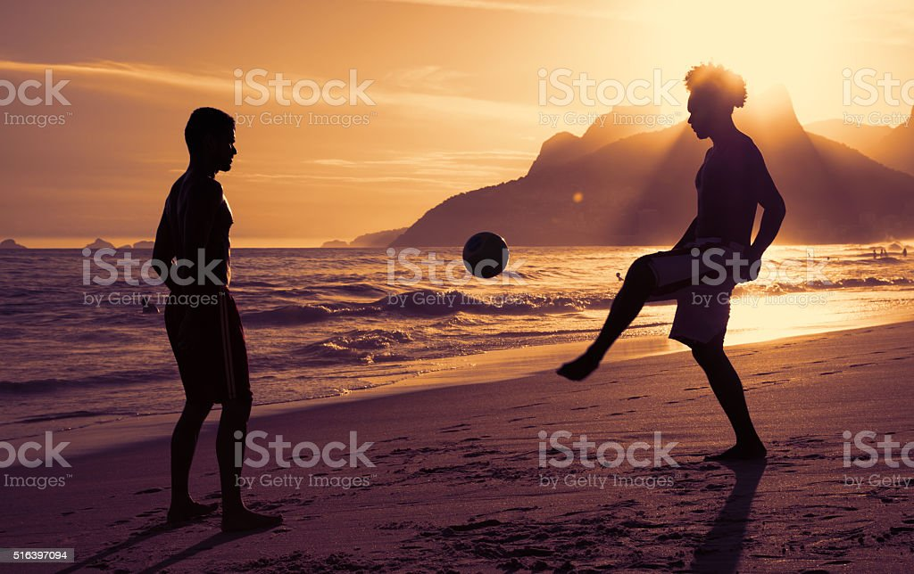 Two guys playing soccer at beach at Rio de Janeiro stock photo
