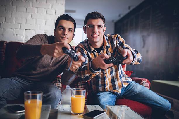 two guys playing video games in office - man joystick imagens e fotografias de stock