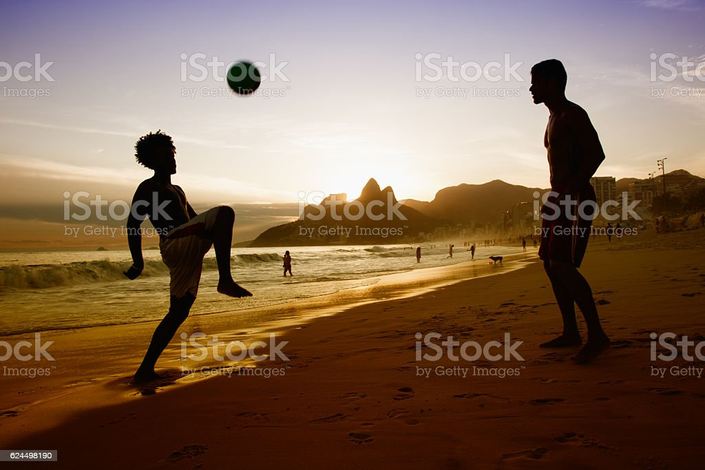 Two guys playing with ball at beach at Rio de Janeiro stock photo