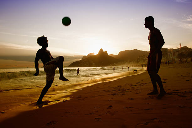 two guys playing with ball at beach at rio de janeiro - futebol de areia - fotografias e filmes do acervo