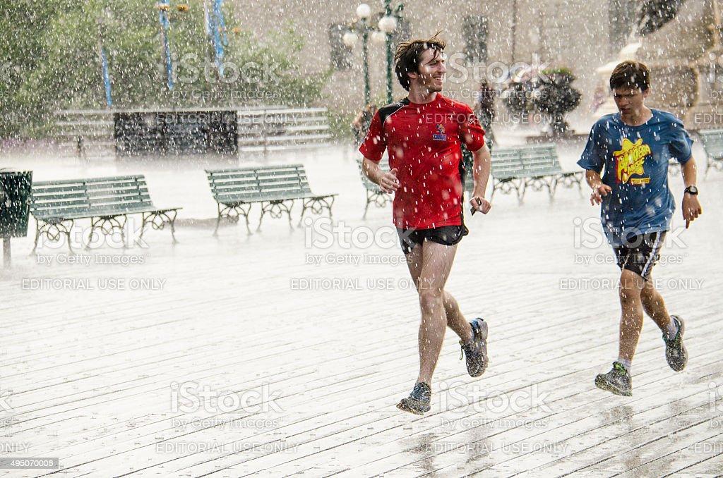 Two guys run in rain in Quebec City, Canada. stock photo
