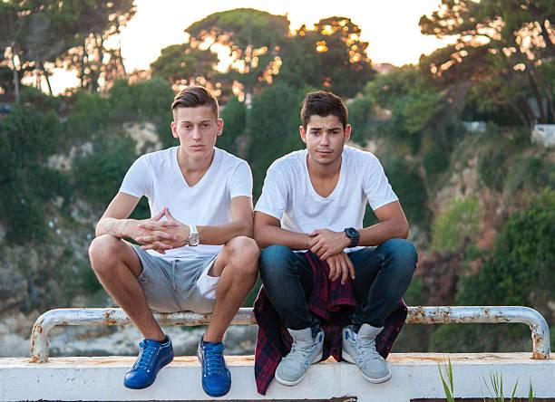 フェンスの上に座って 2 つの男性 - 兄弟 ストックフォトと画像