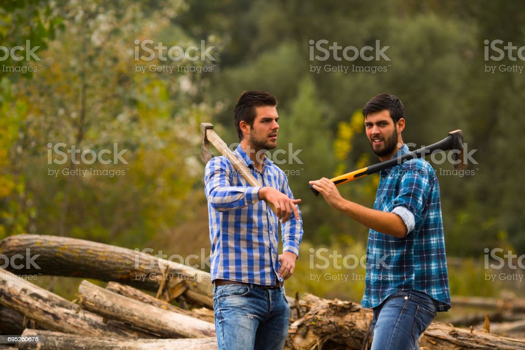 Two guys talking in the forest after logging with axes on their shoulders stock photo
