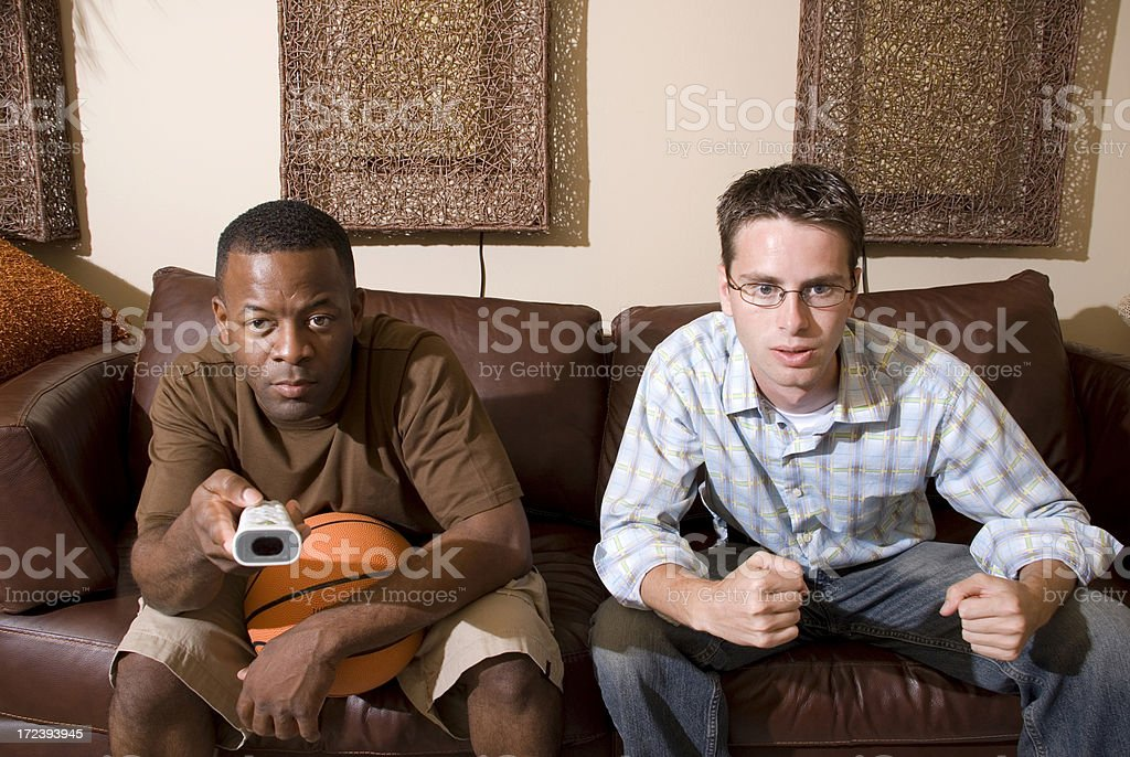Two guys watching television stock photo