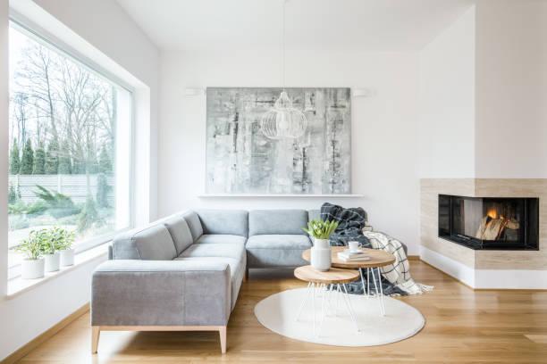 zwei haarnadel mit büchern, tulpen und kaffeetasse tische auf weißen teppich im hellen wohnzimmer interieur mit grauen sofa, kamin und abstrakte gemälde an der wand - kamin wohnzimmer stock-fotos und bilder