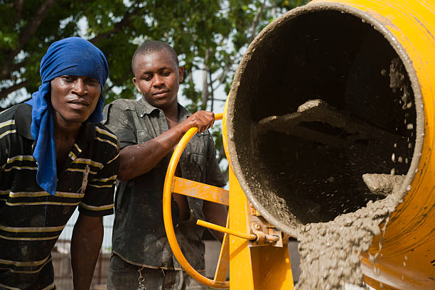 Two haitian construction workers Leogane, Haiti - June 28, 2011: Two young haitian men working on a concrete mixer producing cement. They are rebuilding a house. haitian ethnicity stock pictures, royalty-free photos & images