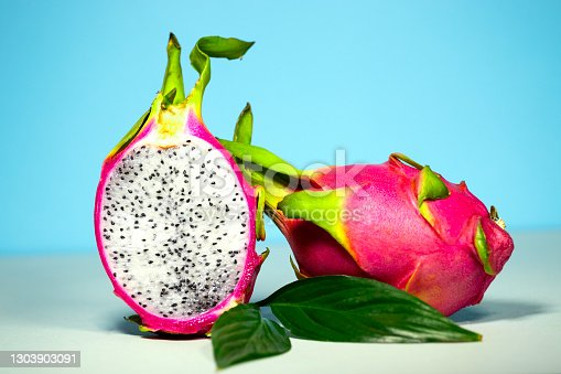 Halves of Fresh organic Dragon Fruit on a blue background, creative summer food concept, banner background with copy space, Minimalism Trendy Food, Colourful and Delicious Pitahaya, Perfect top view of halves of fruit