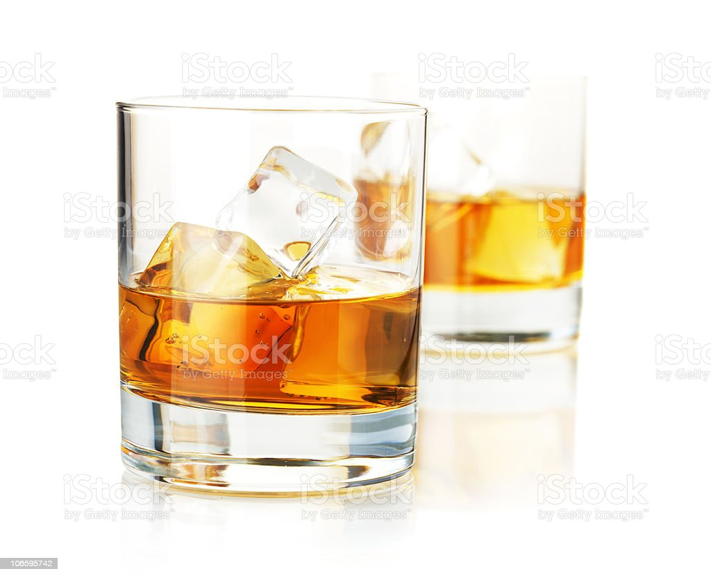 Two half-filled hgh ball glasses of whiskey with ice royalty-free stock photo