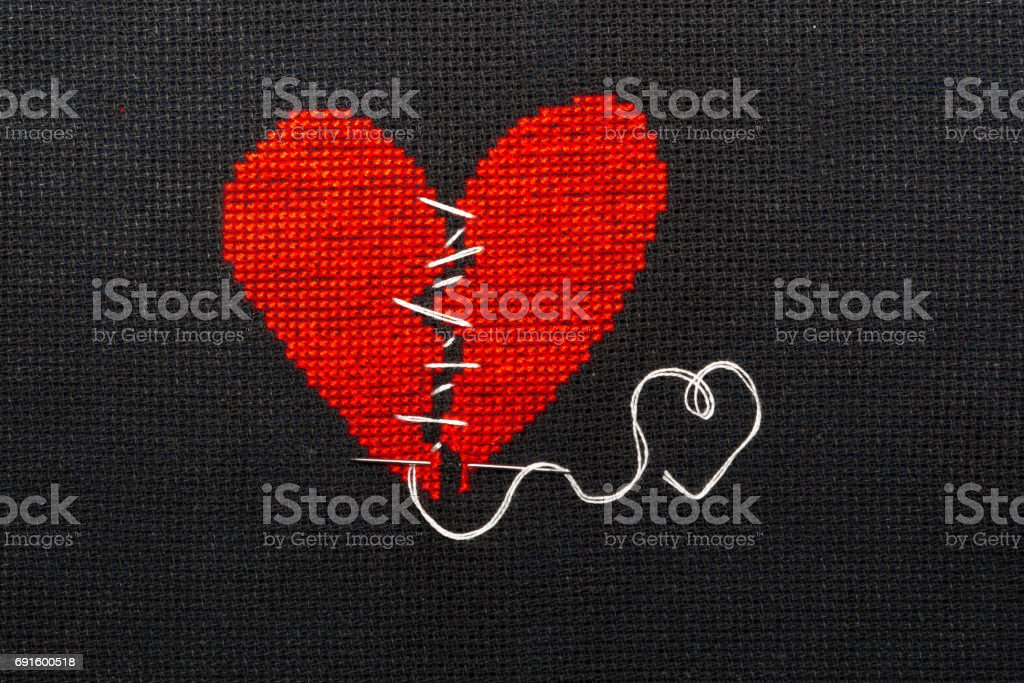 Two halves heart embroidered red thread on black fabric. Two halves heart sewn with black thread. stock photo