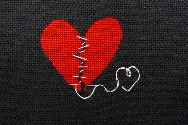 two halves heart embroidered red thread on black fabric. two halves heart sewn with black thread. - chiedere scusa foto e immagini stock