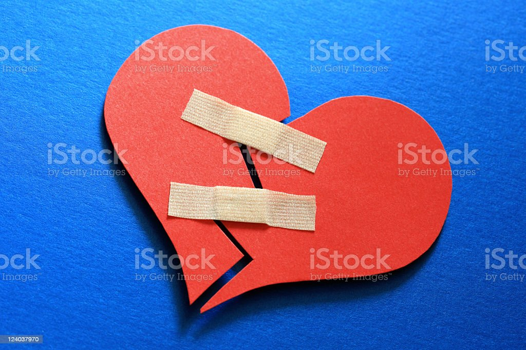 Two halves of a broken paper heart mended with two band aids stock photo
