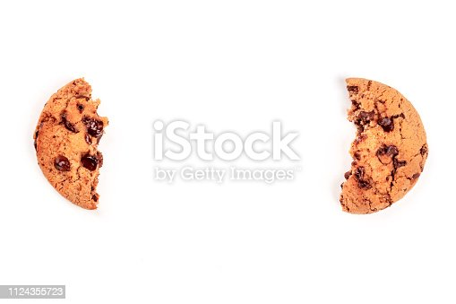 Two halves of a chocolate chip cookie, shot from above on a white background, like brackets, forming a frame for copy space