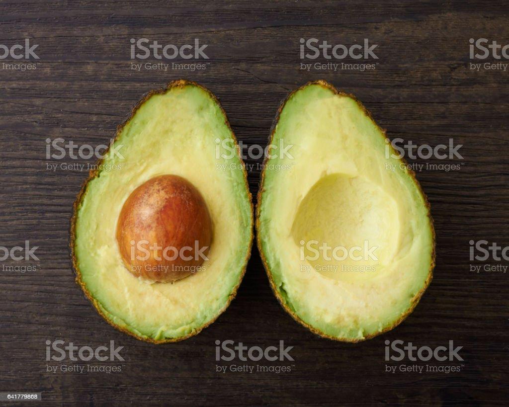 Duas metades de um abacate cortado em uma superfície de madeira - foto de acervo