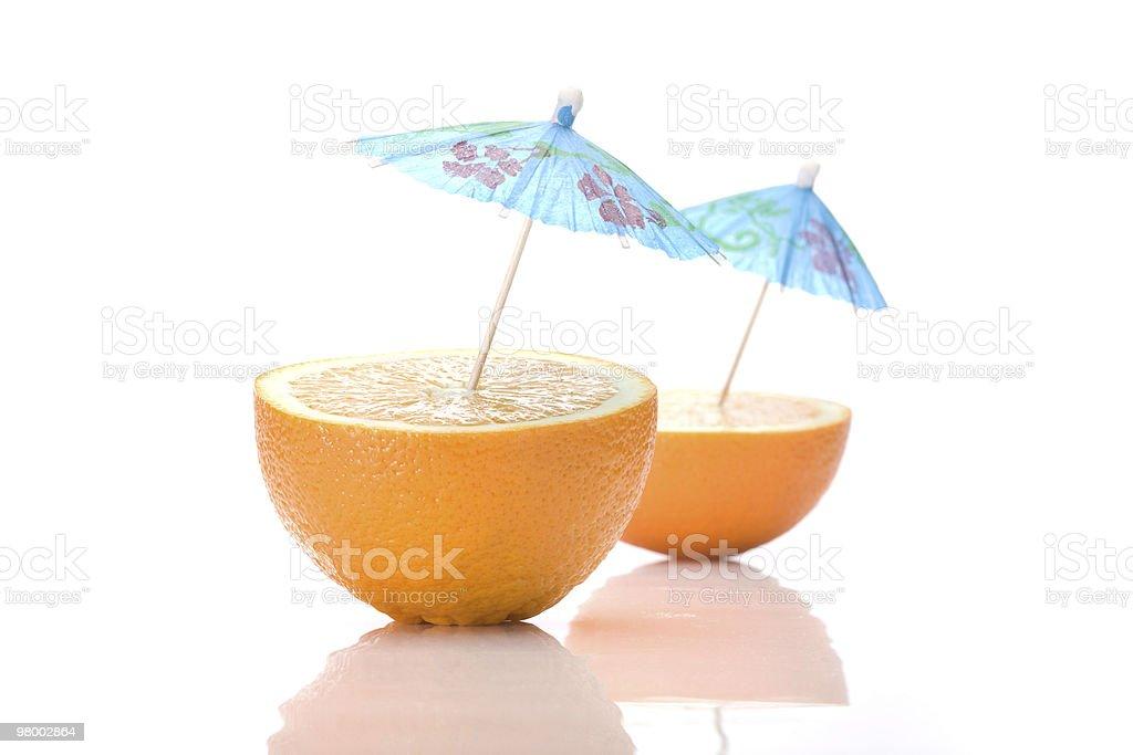 Two halves of an orange with cocktail umbrellas royalty free stockfoto