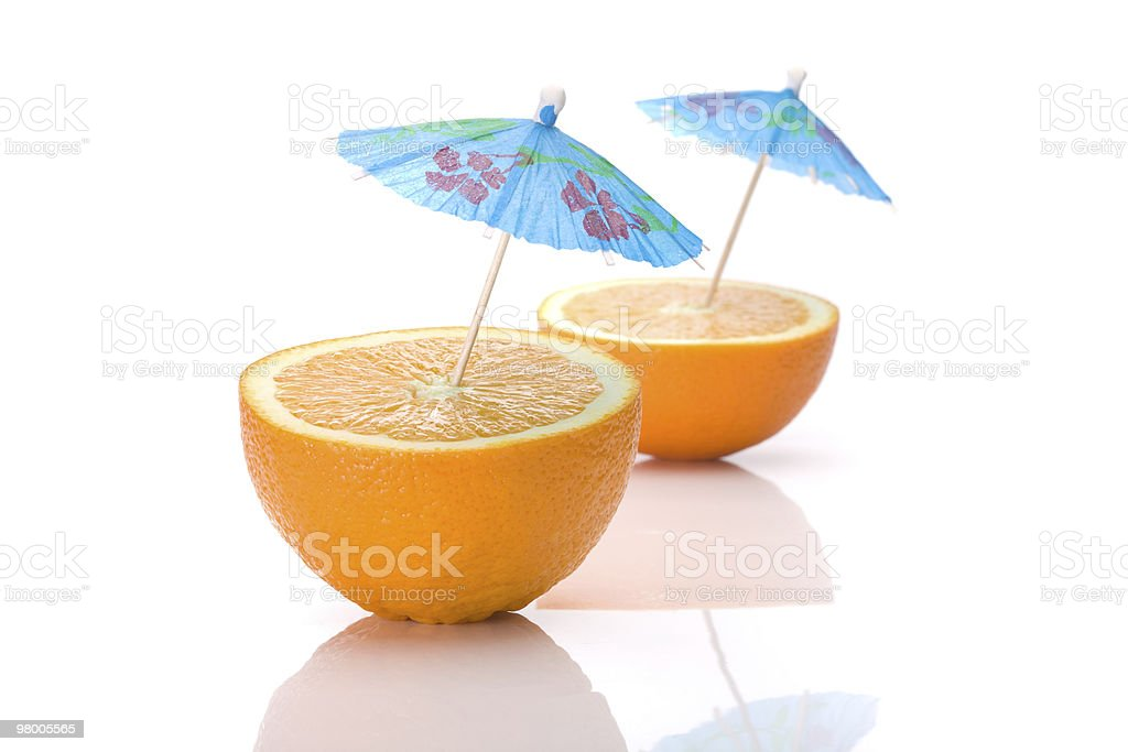 Two halves of an orange with cocktail umbrellas royalty free stockfoto
