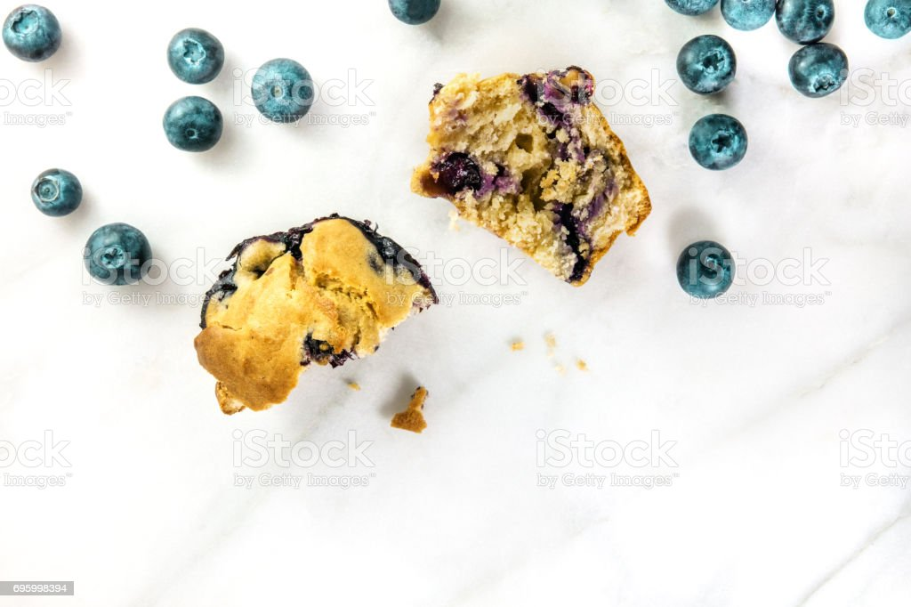 Two halves of blueberry muffin with fresh berries and copyspace stock photo