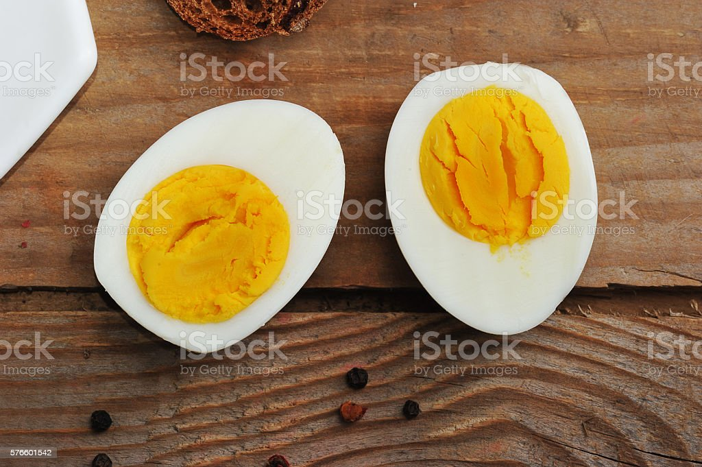 two halves of boiled eggs on wooden rustic background stock photo