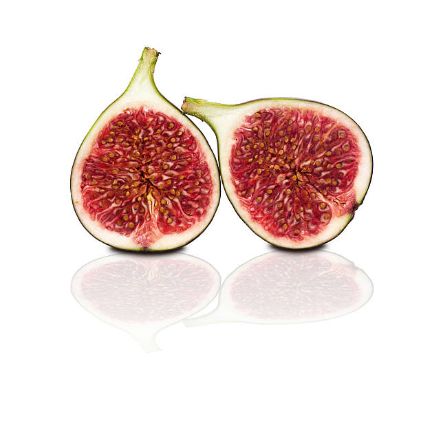 two halves of figs isolated on white background stock photo
