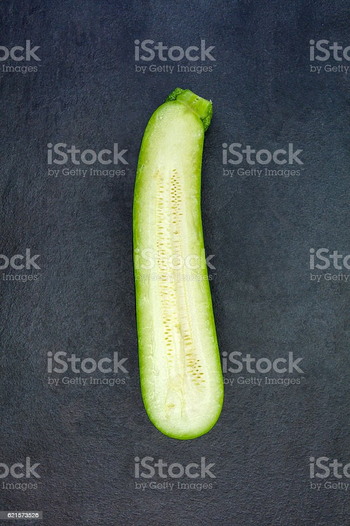 Two halves of fresh green zucchini isolated on gray slate photo libre de droits