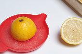 レモン ジュースの 2 つの半分。手動ジューサー。白地。