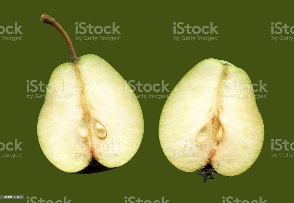 Two halves of one fruit pears isolated on green background. stock photo
