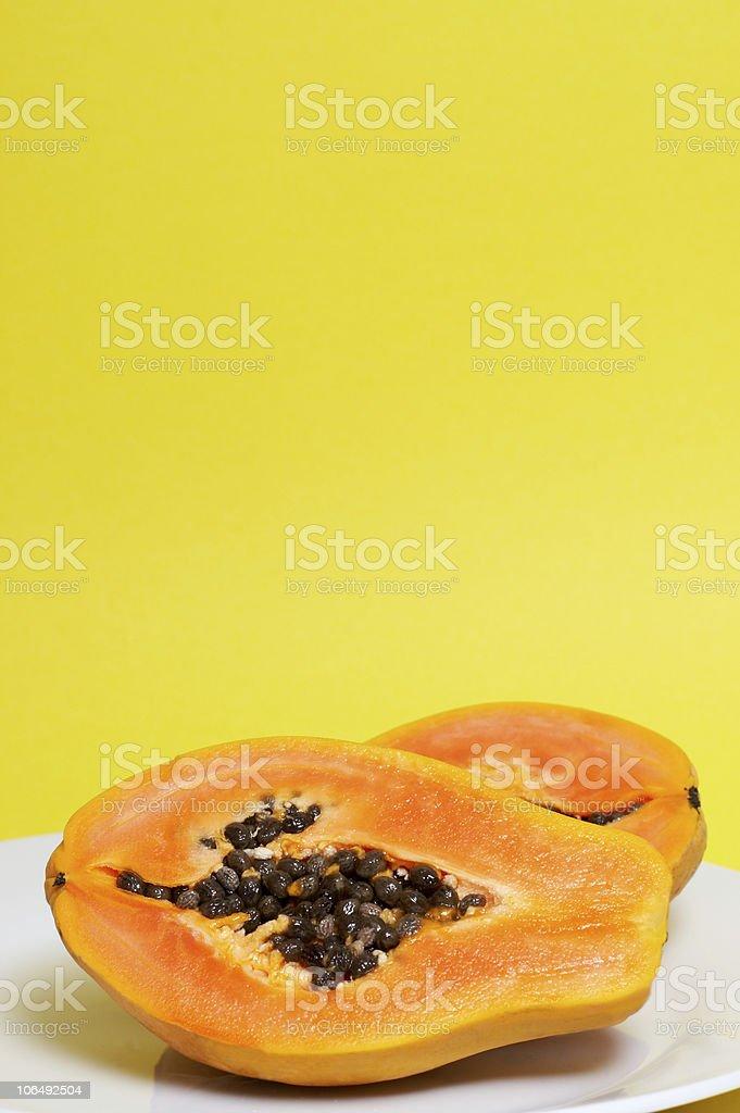 Two halves of papaya on yellow royalty-free stock photo