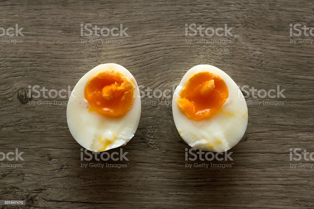 Two halves of soft boiled egg. Directly above view. stock photo