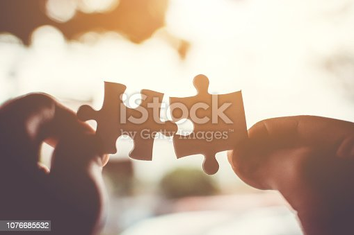 istock Two hand connecting jigsaw puzzle. Concept of partnership and teamwork in business strategy 1076685532
