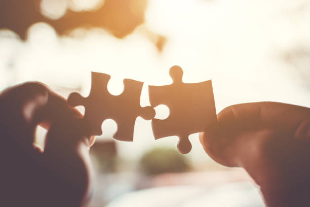 Two hand connecting jigsaw puzzle. Concept of partnership and teamwork in business strategy stock photo
