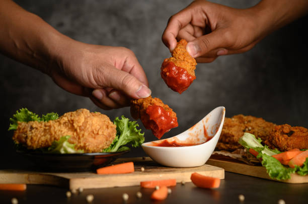 Two hand holding crispy fried chicken dipped in tomato sauce.Selective focus. stock photo