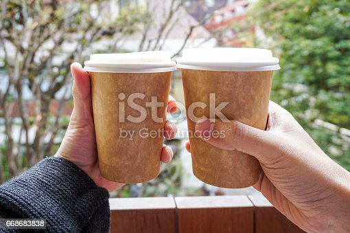 istock Two hand holding hot coffee cup 668683838