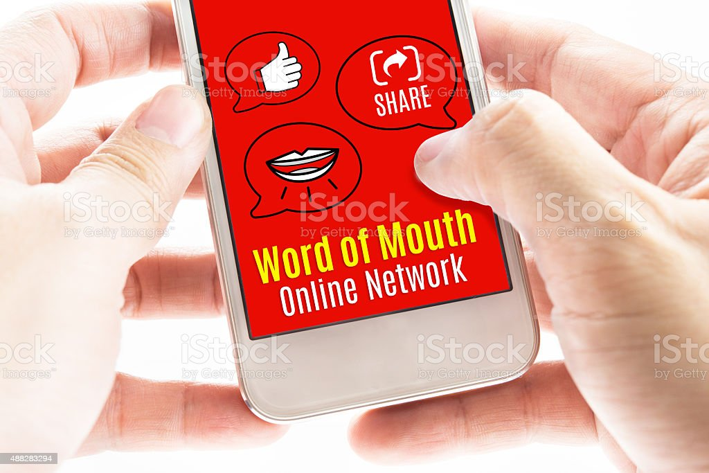 Two hand holding smart phone with word of mouth online stock photo