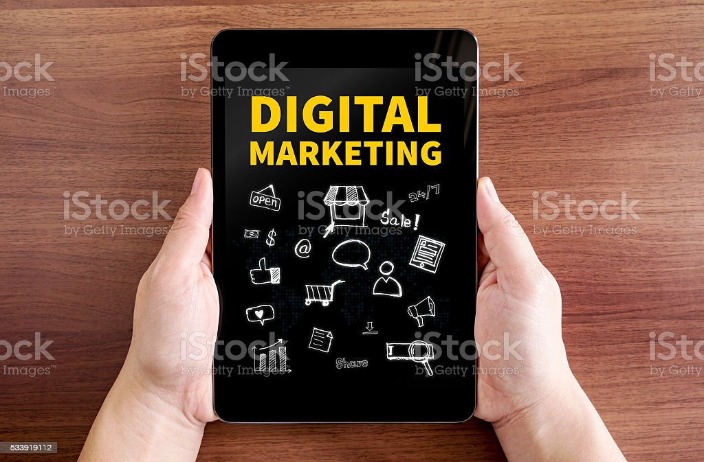 Two hand holding tablet with Digital marketing and doodle icon stock photo