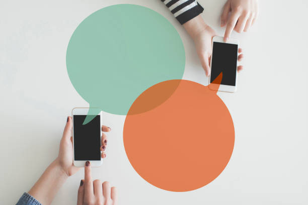 two hand mobile phones sending message each other - perito foto e immagini stock