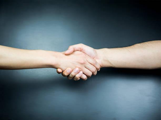 Two handed handshake on black background stock photo