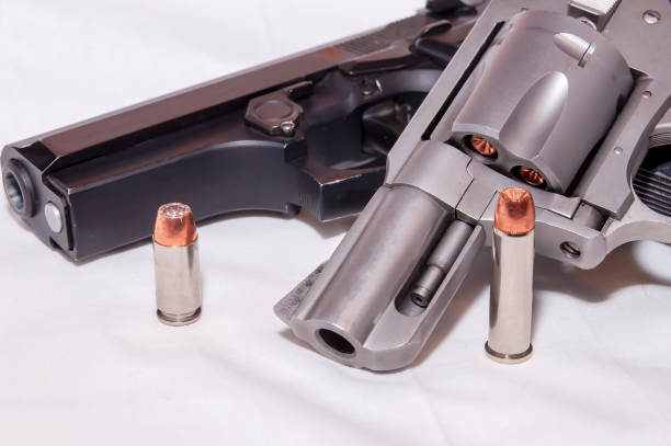 Two handguns, a 357 magnum revolver and a black 40 caliber pistol each with a hollow point bullet next to it stock photo