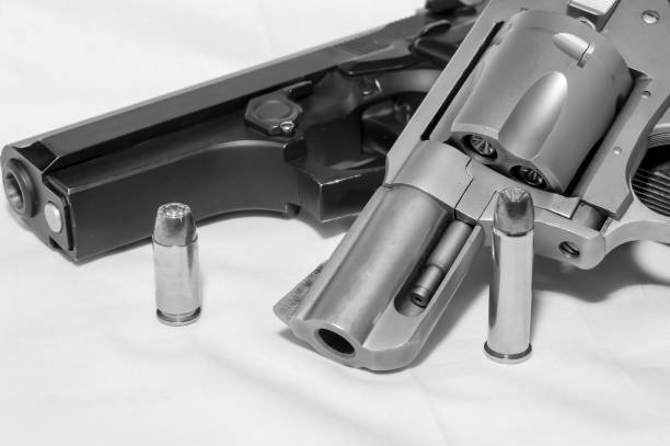 Two handguns, a 40 caliber pistol and a 357 magnum revolver along with a bullet for each stock photo