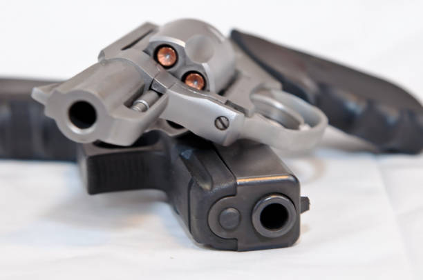 Two handguns, a black 9mm pistol and a silver 357 magnum revolver stock photo