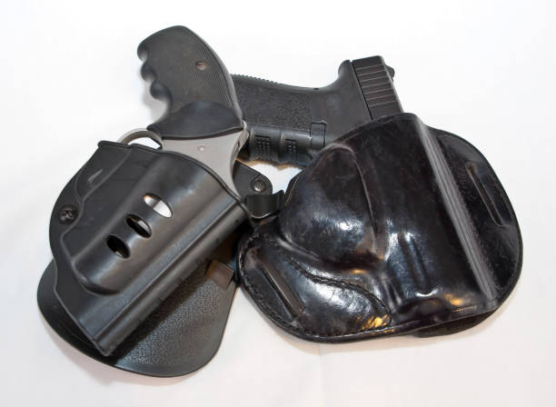 Two handguns, a pistol and a revolver shown in black holsters stock photo