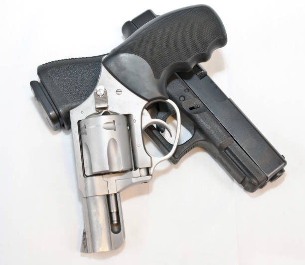 Two handguns, a silver 357 magnum revolver on top of a black 9mm pistol stock photo