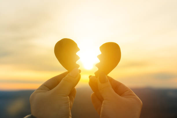 Two hands and a broken heart on a sunset background. stock photo
