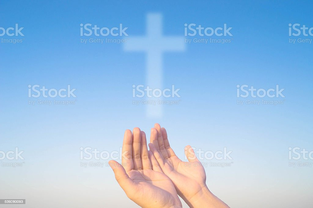 two hands and cross of christ and believers stock photo