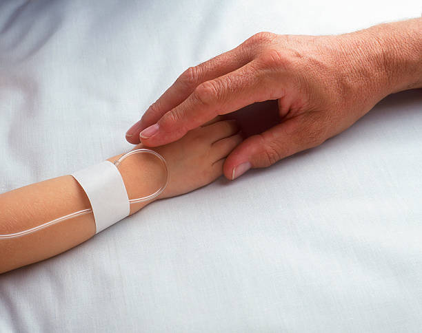 Two hands clasping on hospital bed Adult hand holding sick child's hand with I.V. saline drip stock pictures, royalty-free photos & images